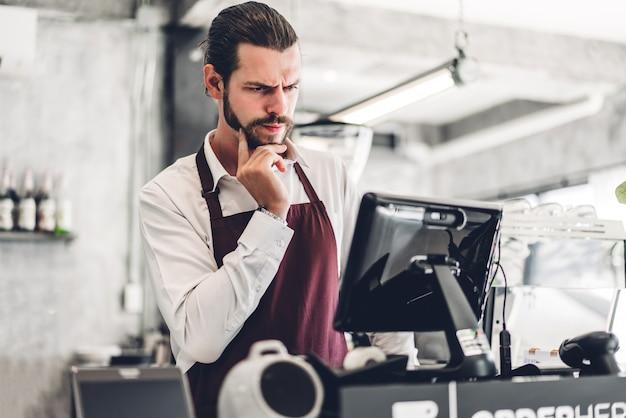 Ritratto di bello barbuto barista uomo piccolo imprenditore che lavora dietro il bancone in un bar