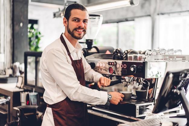 Ritratto di bello barbuto barista uomo piccolo imprenditore che lavora utilizzando la macchina per il caffè per fare il caffè dietro il bancone bar in una caffetteria