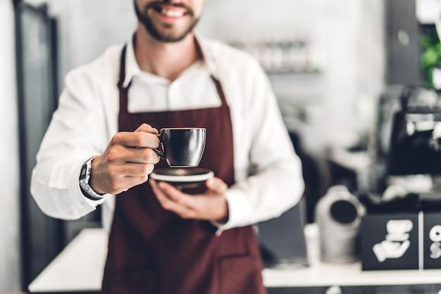 Ritratto di uomo barbuto bello barista piccolo sorridente e tenendo la tazza di caffè nella caffetteria