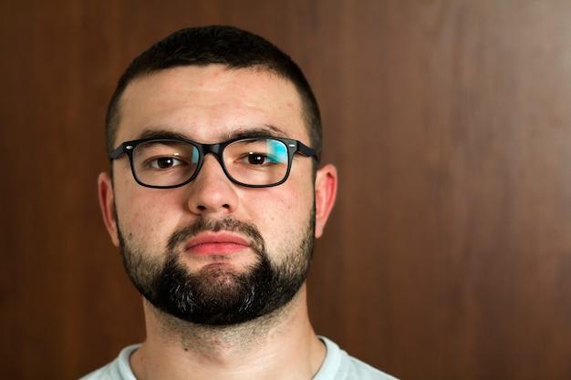 Ritratto di giovane dai capelli neri barbuto bello in occhiali con taglio di capelli corto e occhi neri gentili