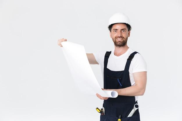 Ritratto di un bel costruttore barbuto che indossa tute in piedi isolato su un muro bianco, guardando la bozza