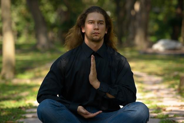 Ritratto di uomo d'affari barbuto bello con i capelli lunghi rilassante al parco all'aperto