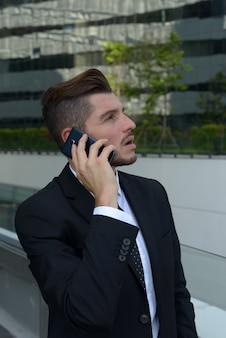 Ritratto di uomo d'affari ispanico barbuto bello contro la vista della città