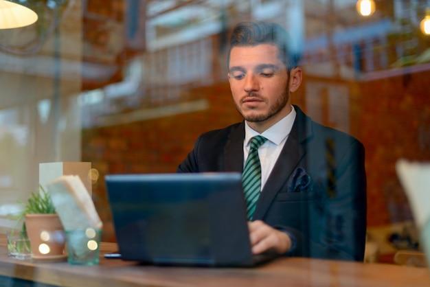 Ritratto di uomo d'affari ispanico barbuto bello rilassante presso la caffetteria