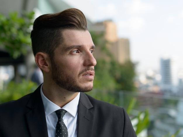 Ritratto di uomo d'affari ispanico barbuto bello con la natura nella città all'aperto