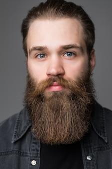 Ritratto di uomo barbuto bello isolato su sfondo grigio
