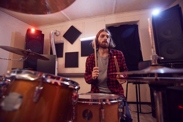Ritratto di uomo barbuto bello suonare la batteria con banda di musica contemporanea