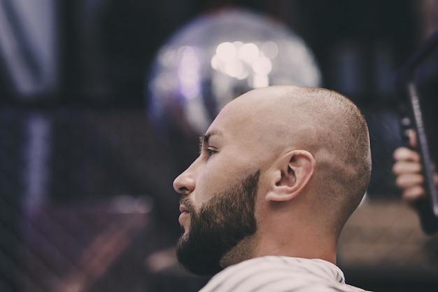 Ritratto di un bell'uomo barbuto seduto su una sedia in un negozio di barbiere