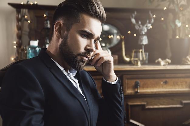 Ritratto dell'uomo barbuto bello che porta vestito classico nero