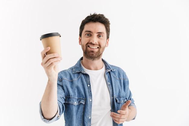Ritratto di un bell'uomo barbuto che indossa abiti casual in piedi isolato, bevendo caffè da asporto