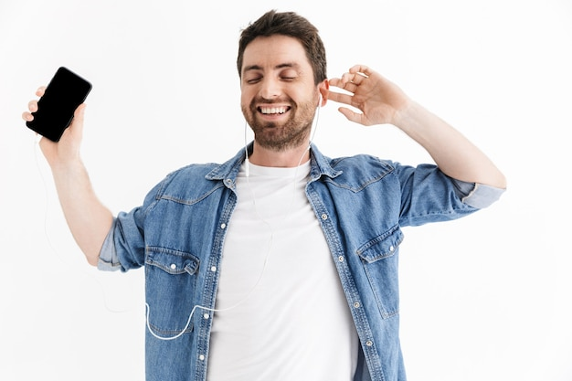 Ritratto di un bell'uomo barbuto che indossa abiti casual in piedi isolato, ascolta musica con gli auricolari, tiene in mano un telefono cellulare vuoto