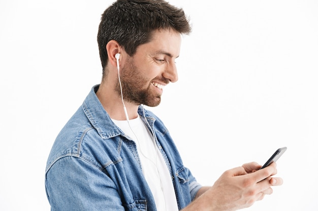 Ritratto di un bell'uomo barbuto che indossa abiti casual in piedi isolato, ascolta musica con gli auricolari, tiene in mano il cellulare