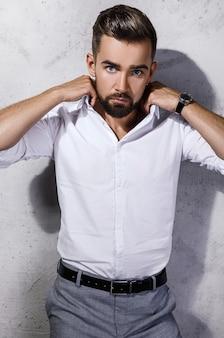 Ritratto di uomo barbuto bello che indossa una camicia bianca è in posa contro il muro di cemento