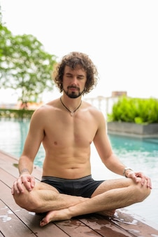 Ritratto di uomo barbuto bello con capelli ricci a torso nudo rilassante accanto alla piscina nella città di bangkok, thailandia