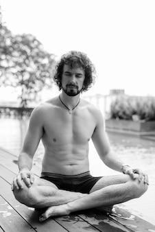 Ritratto di un bell'uomo barbuto con i capelli ricci a torso nudo che si rilassa accanto alla piscina