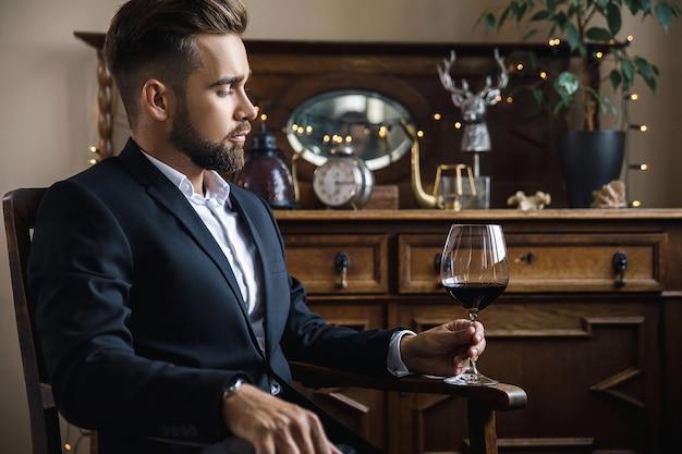 Ritratto di uomo barbuto bello con un bicchiere di vino rosso
