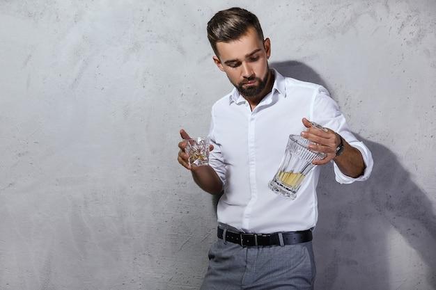 Ritratto di uomo barbuto bello con un bicchiere di whisky
