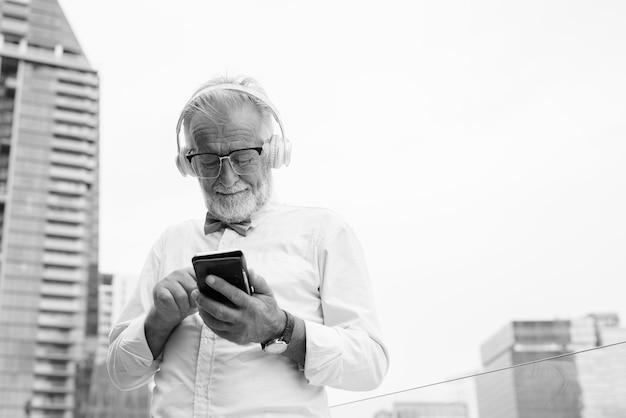 Ritratto di bello barbuto turista anziano uomo che indossa abiti eleganti mentre esplora la città di bangkok in bianco e nero