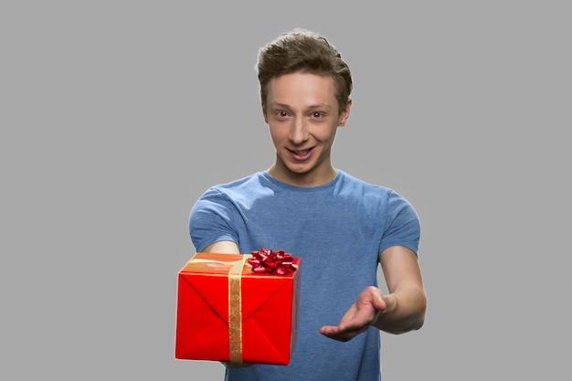 Ritratto del ragazzo bello che offre confezione regalo. ragazzo teenager sveglio che tiene casella attuale. offerta speciale per le vacanze.