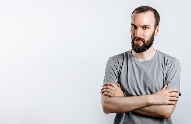 Ritratto di un uomo serio brunetta brutale bello su un muro bianco con le braccia incrociate