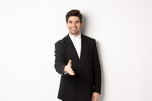 Ritratto di un bell'uomo d'affari in abito nero, che allunga la mano per stretta di mano, saluta i partner commerciali e sorride, benvenuto in compagnia, in piedi su sfondo bianco