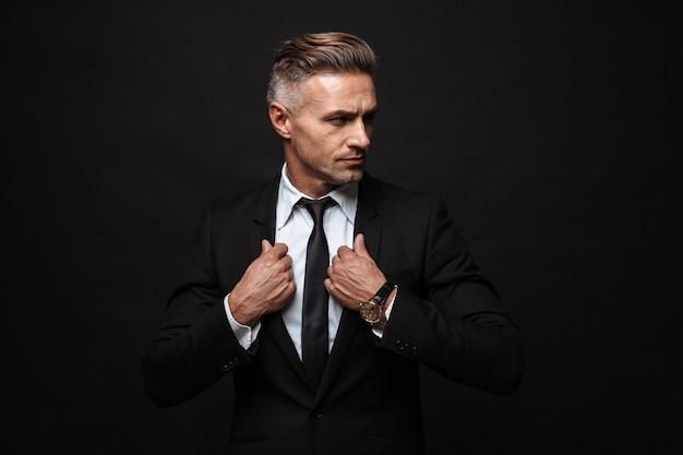 Ritratto di un bell'uomo d'affari vestito con un abito formale che tocca la sua giacca e guarda da parte isolato sul muro nero