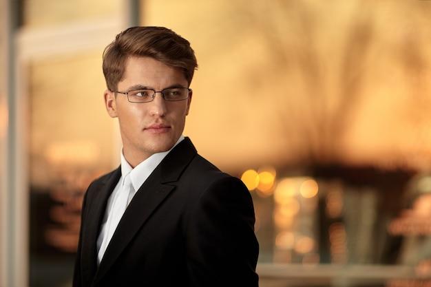 Ritratto di un bell'uomo d'affari in occhiali e abito nero, bellissimo sfondo dorato del tramonto.