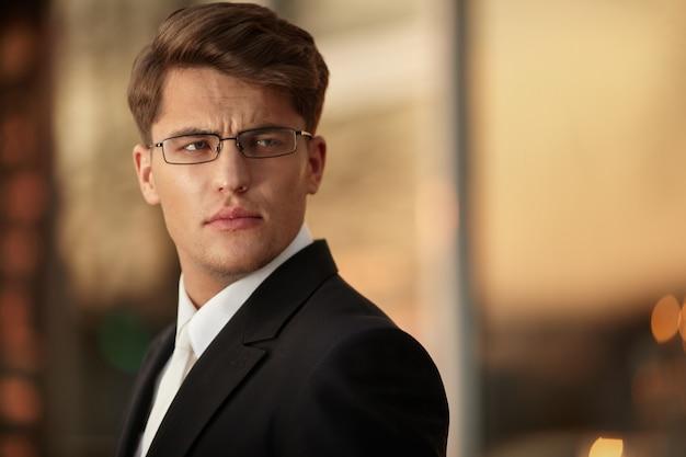 Ritratto di un bell'uomo d'affari in occhiali e abito nero., sfondo tramonto.