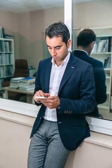 Ritratto di un bell'uomo d'affari che guarda lo smartphone davanti alla finestra dell'ufficio