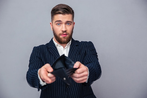 Ritratto di un uomo d'affari bello che mostra il suo portafoglio vuoto sopra il muro grigio
