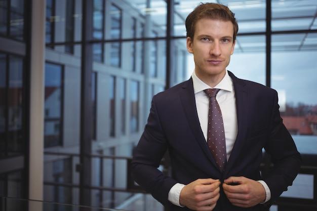 Ritratto di uomo d'affari bello in piedi nel corridoio