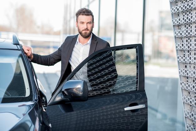 Ritratto di un bell'uomo d'affari in piedi vicino all'auto all'aperto vicino alla moderna facciata dell'edificio