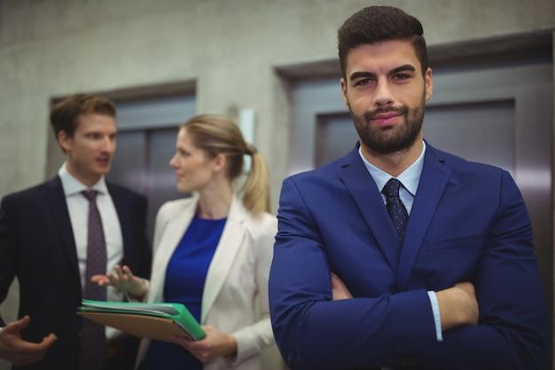 Ritratto di uomo d'affari bello in piedi con le braccia incrociate