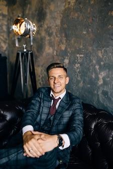 Ritratto di un uomo d'affari bello in vestito su un divano in pelle vintage di lusso
