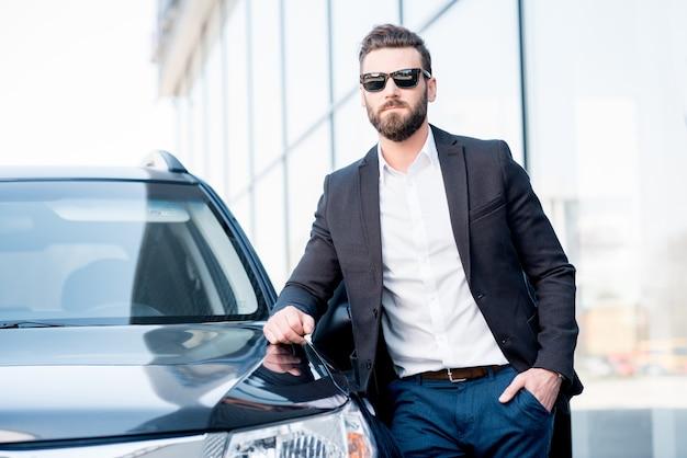 Ritratto di un bell'uomo d'affari con gli occhiali da sole in piedi vicino all'auto all'aperto di fronte alla moderna facciata dell'edificio