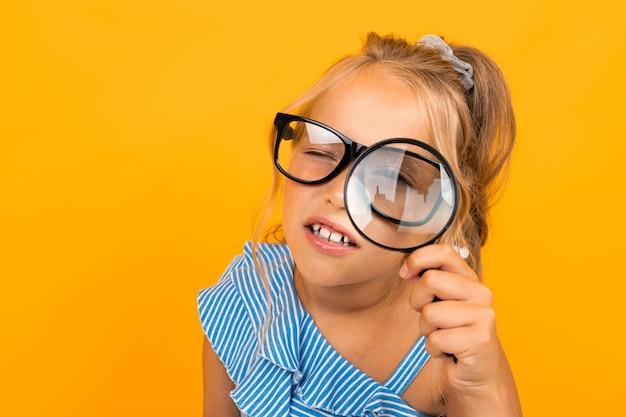 Ritratto di bella ragazza caucasica con lunghi capelli biondi e bel viso in abito blu cerca di guardare attraverso gli occhiali