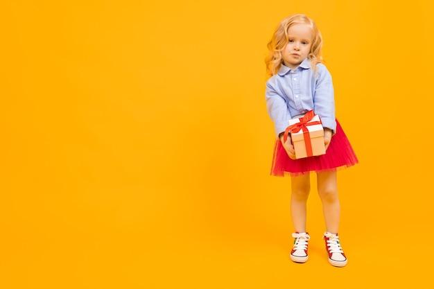 Ritratto di bella ragazza caucasica con lunghi capelli biondi, bel viso in abito esulta e tiene una scatola bianca con un regalo
