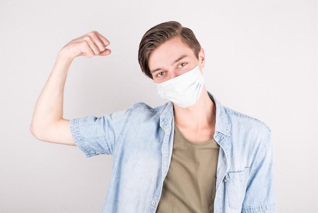 Ritratto di un bell'uomo caucasico che indossa la maschera protettiva medica in piedi con un braccio alzato mostra bicipiti.