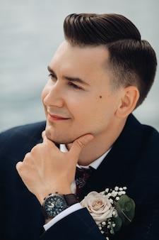 Ritratto di uomo caucasico bello con capelli scuri corti cerca la fotocamera e il sorriso