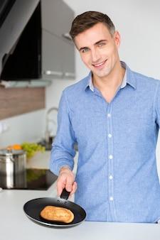 Ritratto di un bell'uomo allegro che prepara frittelle in cucina a casa