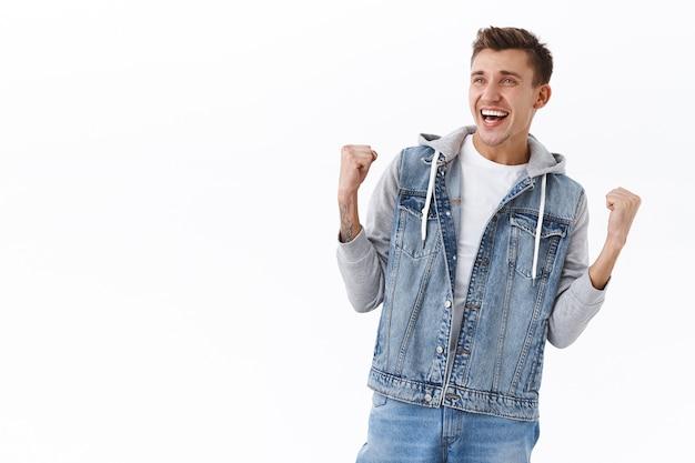 Ritratto di un bell'uomo biondo allegro e trionfante in giacca di jeans, pompa a pugno raggiunge l'obiettivo, guardando lo schermo della tv al pub mentre guarda la scommessa vincente di una partita sportiva, diventa campione, celebra la vittoria