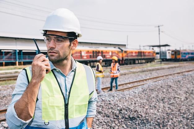 Ritratto di un bell'ingegnere che utilizza un walkie talkie per il controllo della ferrovia del treno