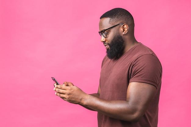 Ritratto di bello eccitato allegro gioioso delizioso ragazzo nero afroamericano che indossa l'invio casuale e riceve messaggi al suo amante isolato su sfondo rosa. usando il telefono.