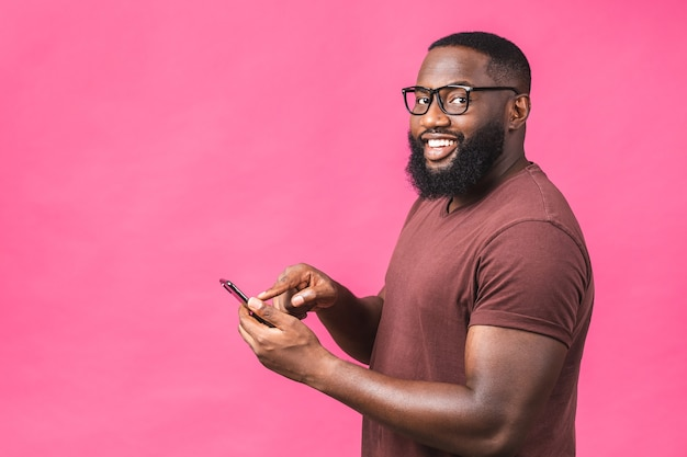Ritratto di bello eccitato allegro gioioso delizioso ragazzo afroamericano che indossa l'invio casuale e riceve messaggi al suo amante isolato su sfondo rosa. usando il telefono.