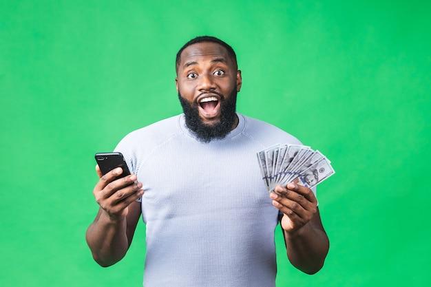 Ritratto di bello eccitato allegro gioioso delizioso ragazzo afroamericano che indossa casual invio e ricevere messaggi al suo amante isolato su sfondo verde. usando il telefono.