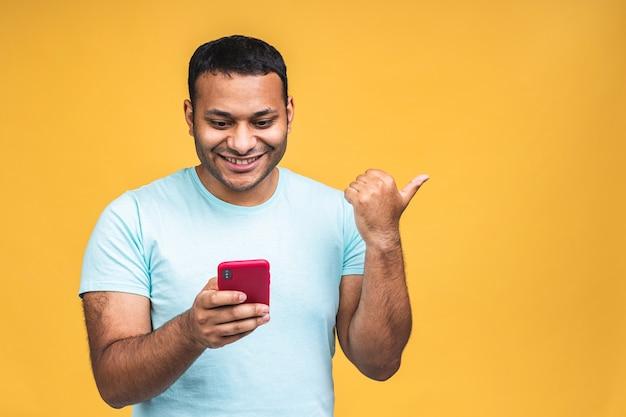 Ritratto di bello eccitato allegro gioioso ragazzo afroamericano indiano che indossa l'invio casuale e riceve messaggi al suo amante isolato su sfondo giallo. usando il telefono. dito puntato.
