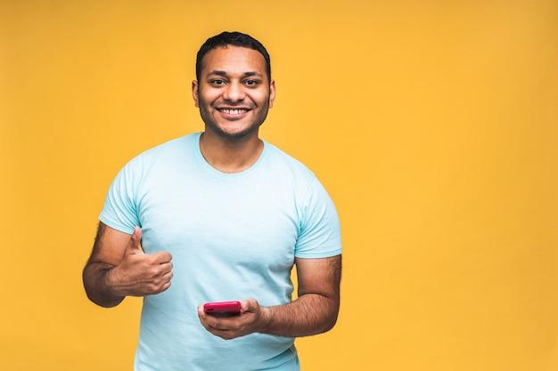 Ritratto di bello eccitato allegro gioioso ragazzo afroamericano indiano che indossa l'invio casuale e riceve messaggi al suo amante isolato su sfondo giallo. usando il telefono. pollice su.