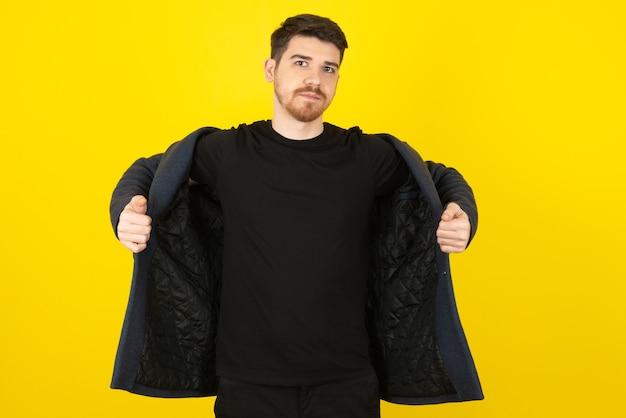 Ritratto di un bel ragazzo che cerca di indossare la giacca su un giallo.