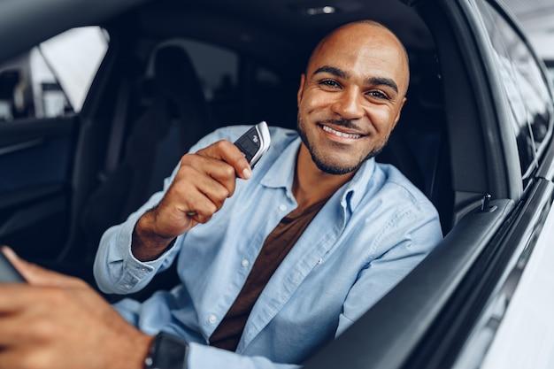 Ritratto di un uomo afroamericano felice bello seduto nella sua auto appena acquistata