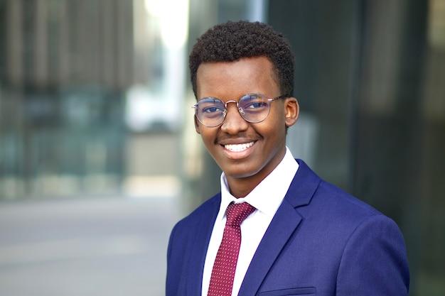 Ritratto di bello felice fiducioso nero giovane afroamericano uomo d'affari afroamericano ufficio all'aperto